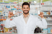 Handsome pharmacist smiling at camera and holding jars with pills