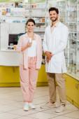 Fotografie Kundin mit Pillen im Glas und Apothekerin lächelt in Kamera mit Apothekenvitrine im Hintergrund