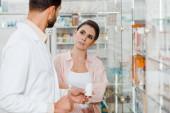 Fotografie Kundin mit verschränkten Armen schaut Apotheker mit Pillen in Drogerievitrine an