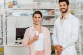Smiling woman with jar of pills beside pharmacist with drugstore showcase at background