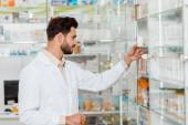 Seitenansicht eines hübschen Apothekers, der neben Regalen mit Medikamenten ein Gefäß mit Pillen betrachtet