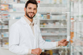 Smiling druggist holding jar with pills while looking at camera beside pharmacy showcase