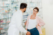 Druggist helping pregnant woman with pharmacy showcase at background