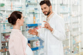 Smiling pharmacist showing to pregnant woman jar with pills by drugstore showcase
