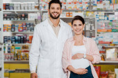 Smiling pharmacist and pregnant woman looking at camera with pharmacy showcase at background