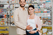 Smiling man hugging pregnant wife and looking at camera in pharmacy