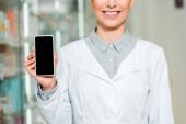 Fotografie Ausgeschnittene Ansicht eines lächelnden Apothekers mit Smartphone und leerem Bildschirm