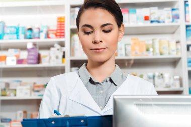 Beautiful pharmacist writing on clipboard in drugstore
