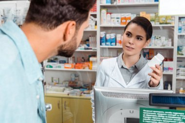 Selective focus of pharmacist showing jar of pills to customer at drugstore counter