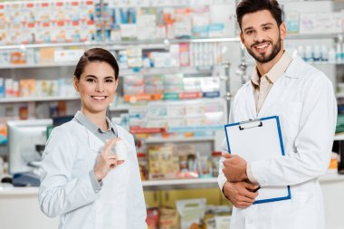 Smiling pharmacists with clipboard and pills looking at camera in drugstore