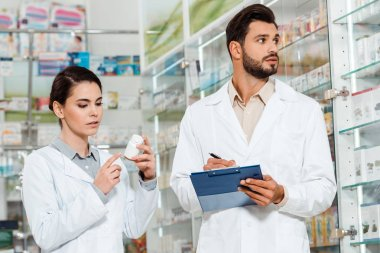 Pharmacist with clipboard and colleague with pills by pharmacy showcase