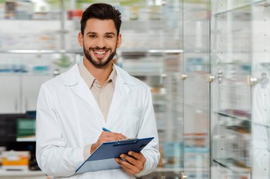 Handsome pharmacist with clipboard smiling at camera by drugstore showcase