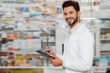 Selective focus of smiling pharmacist with clipboard looking at camera in apothecary