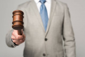 cropped view of judge holding gavel isolated on grey