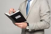Fotografie oříznutý pohled na obchodníka, jak čte knihu s názvem duševního vlastnictví izolovanou na šedé