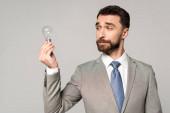 skeptical businessman holding light bulb isolated on grey
