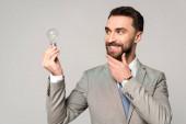 Lächelnder Geschäftsmann berührt Gesicht, während er Glühbirne isoliert auf grau hält