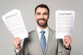 glücklich Geschäftsmann mit Verträgen und Blick auf Kamera isoliert auf grau