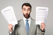 schockierter Geschäftsmann mit Verträgen und Blick auf Kamera isoliert auf grau