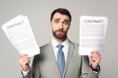 upset businessman holding contracts and looking at camera isolated on grey