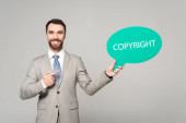 mosolygó üzletember ujjal mutogat a gondolat buborék szerzői jogi felirattal elszigetelt szürke