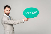 serious businessman holding thought bubble with copyright inscription isolated on grey