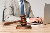 selective focus of gavel near lawyer working at laptop isolated on grey