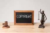 chalkboard with word copyright, themis statue and gavel on wooden desk isolated on grey