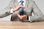 Fotografie abgeschnittene Ansicht eines Geschäftsmannes mit schützender Geste, während er isoliert auf grau am Schreibtisch sitzt