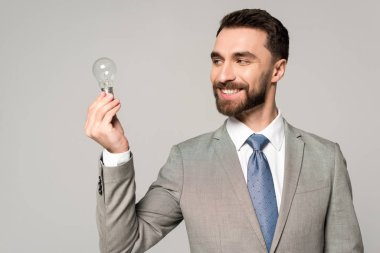 Smiling businessman holding light bulb isolated on grey stock vector