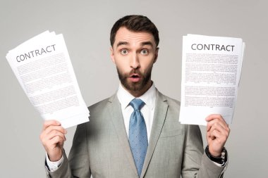 Shocked businessman holding contracts and looking at camera isolated on grey stock vector
