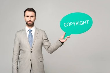 Confident businessman holding thought bubble with copyright inscription isolated on grey stock vector