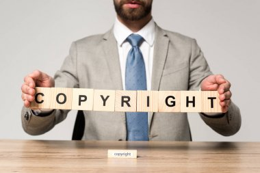 Cropped view of businessman holding wooden cubes with word copyright isolated on grey stock vector