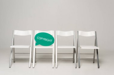 Row of chairs and thought bubble with copyright inscription on grey background stock vector