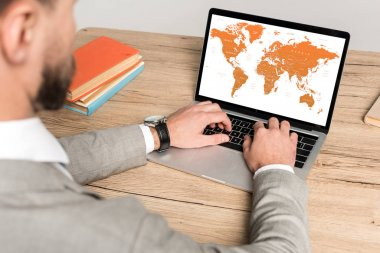 cropped view of businessman using laptop with world map on screen isolated on grey