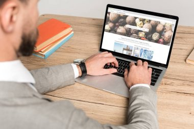 KYIV, UKRAINE - NOVEMBER 25, 2019: cropped view of businessman using laptop with Depositphotos website on screen isolated on grey stock vector
