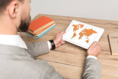 cropped view of businessman using digital tablet with world map on screen isolated on grey