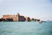 pohled na plovoucí motorové čluny v blízkosti starobylých budov v Benátkách, Itálie