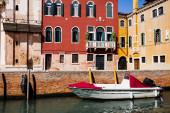 motorový člun v blízkosti světlých a barevných budov v Benátkách, Itálie