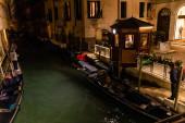 Benátky, Itálie - 24. září 2019: kanál s gondolami v blízkosti starobylé budovy v noci v Benátkách, Itálie