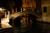 most nad kanálem v blízkosti starobylých budov v noci v Benátkách, Itálie