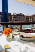 szelektív fókusz borüveg, kenyér és virágok az asztalon és az ősi épületek a háttérben