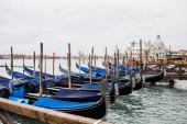řeka, modré gondoly a Santa Maria della Salute v Benátkách, Itálie