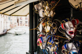 selective focus of carnival masks and motor boat floating on background in Venice, Italy