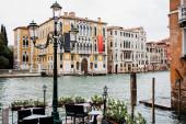Venkovní kavárna s výhledem na kanál a starobylé budovy v Benátkách, Itálie