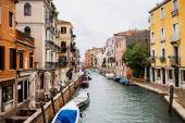 motor boats near ancient and bright buildings in Venice, Italy