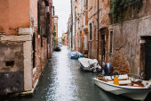 canal, motor boats near ancient buildings in Venice, Italy