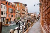 kanál, vaporetto v blízkosti mostu a starobylé budovy v Benátkách, Itálie