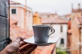 oříznutý pohled na ženu držící šálek kávy v Benátkách, Itálie