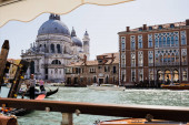VENICE, ITALY - SEPTEMBER 24, 2019: motor boats and gondolas floating on canal near Santa Maria della Salute church
